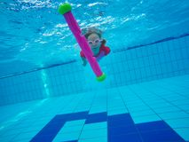 Little girl under water in pool. royalty free stock photography