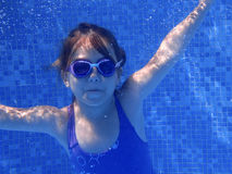 Little girl underwater in the pool Stock Photos