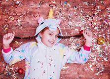 A little girl in a unicorn costume. Christmas concept. Girl lying on a wooden background, a lot of colorful confetti stock photos
