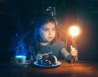 Little girl and the universe. A little girl holds up the sun on her fork royalty free stock images