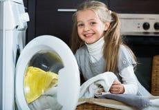 Little girl unloading washing machine and smiling Royalty Free Stock Image