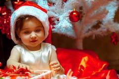 Little girl unpacks the gift under the Christmas tree Stock Photos