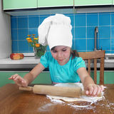 Little girl unrolls the dough Royalty Free Stock Photos