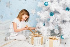 Little girl unties the ribbon on a Christmas present Royalty Free Stock Photography