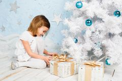 Little girl unties the ribbon on a Christmas present Royalty Free Stock Image