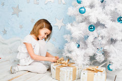 Little girl unties the ribbon on a Christmas present Stock Images