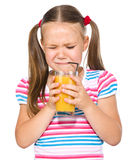 Little girl unwillingly drinking orange juice Royalty Free Stock Images