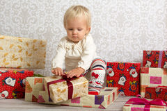Little girl unwrapping Christmas present. An adorable baby girl concentrate when unwrapping Christmas gift Royalty Free Stock Photography
