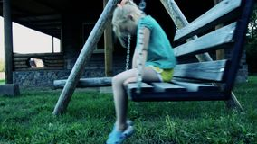The little girl is upset on the swings. offense stock video footage