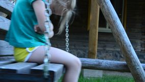 The little girl is upset on the swings. offense stock footage