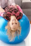 Little girl upside down on fit ball laughing Royalty Free Stock Image