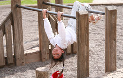 Little girl upside down at playground royalty free stock photo