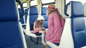 Little girl use a smartphone and sitting in front of her mom in the train. Close up stock video footage