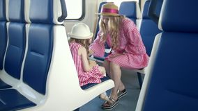 Little girl use a smartphone and sitting in front of her mom in the train. Close up stock footage