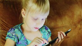 A little girl uses a digital tablet. The light from the screen illuminates her face.  stock video