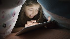 Little girl uses digital tablet under cover, at night. Little girl uses digital tablet under cover at night. Screen illuminates her face. The girl is having fun stock footage