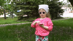 Little girl uses a pink phone in the park. stock footage