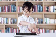 Little girl uses tablet in library Royalty Free Stock Image