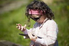 Little girl uses tablet outdoors Royalty Free Stock Images
