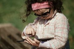 Little girl uses tablet outdoors Stock Photos