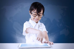 Little girl uses tablet with world map background Stock Image