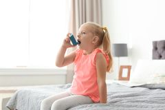 Little girl using asthma inhaler. In bedroom royalty free stock images
