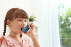 Little girl using asthma inhaler. On blurred background stock image