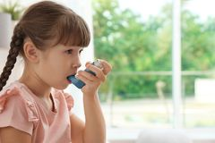 Little girl using asthma inhaler. On blurred background royalty free stock photos