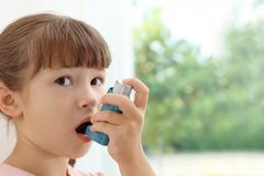 Little girl using asthma inhaler. On blurred background royalty free stock photo