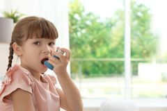 Little girl using asthma inhaler. On blurred background stock images