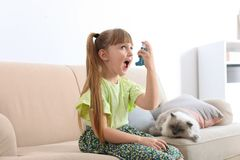 Little girl using asthma inhaler near cat at home. Health care stock images