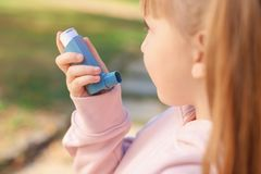 Little girl using asthma inhaler outdoors. Health care royalty free stock image