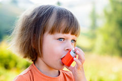 Girl using asthma inhaler Stock Images