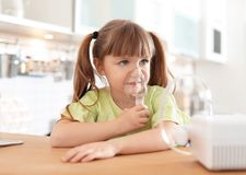 Little girl using asthma machine at table. In kitchen stock photos