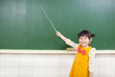 Little girl using a baton to point on a blackboard Stock Photo