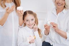 Little girl using beauty cream. Stock Photo