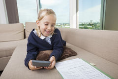 Little girl using calculator while studying on sofa Royalty Free Stock Images