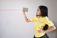 Little girl using a can as telephone. On a gray background Royalty Free Stock Image