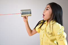 Little girl using a can as telephone Royalty Free Stock Image