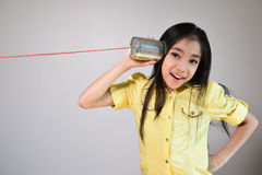 Little girl using a can as telephone Royalty Free Stock Photos