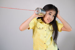 Little girl using a can as telephone Stock Photography