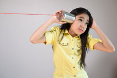 Little girl using a can as telephone Stock Image