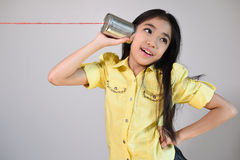 Little girl using a can as telephone Royalty Free Stock Photography