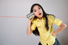 Little girl using a can as telephone Stock Photos
