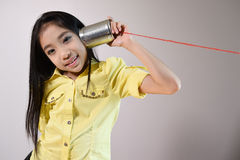 Little girl using a can as telephone Royalty Free Stock Images