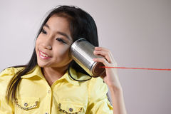 Little girl using a can as telephone Stock Photo