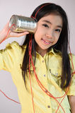 Little girl using a can as telephone Stock Images