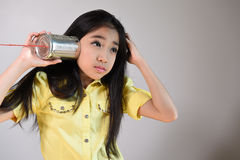 Little girl using a can as telephone. On a gray background Stock Photo