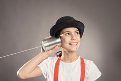 Little girl using a can as telephone. On a gray background Royalty Free Stock Images
