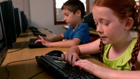 Little girl using computer in classroom in school Stock Photo